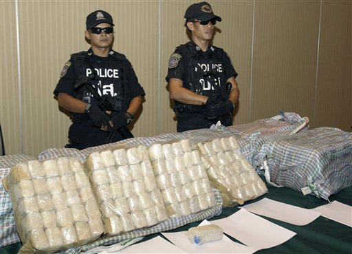 FILE - In this March 16, 2012 file photo, Thai policemen guard packages containing about 2 million methamphetamine pills seized in Lampang province, prior to a press conference at the police headquarters in Bangkok, Thailand. Seizures of crystal meth and methamphetamine pills reached record highs in East and Southeast Asia in 2012, with Myanmar retaining its status as a major supplier of the illicit drugs, the United Nations said Friday, Nov. 8, 2013. (AP Photo/Sakchai Lalit, File)