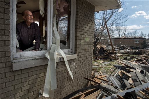 Chuck Phillips looks out at the destruction that tore off part of his roof and left houses around him destroyed after a tornado left a path of devastation through the north end of Pekin, Il.,Sunday, Nov. 17, 2013. Intense thunderstorms and tornadoes swept across the Midwest on Sunday, causing extensive damage in several central Illinois communities while sending people to their basements for shelter. (AP Photo/Journal Star, Fred Zwicky)