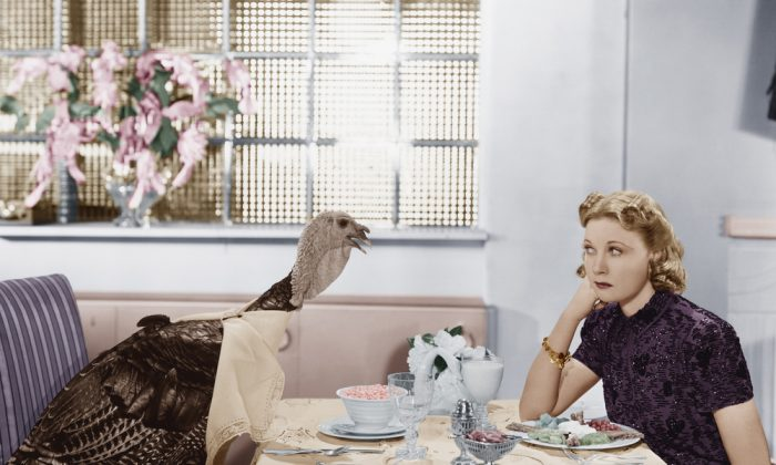Woman eating meal at table with live turkey Image via Shutterstock*