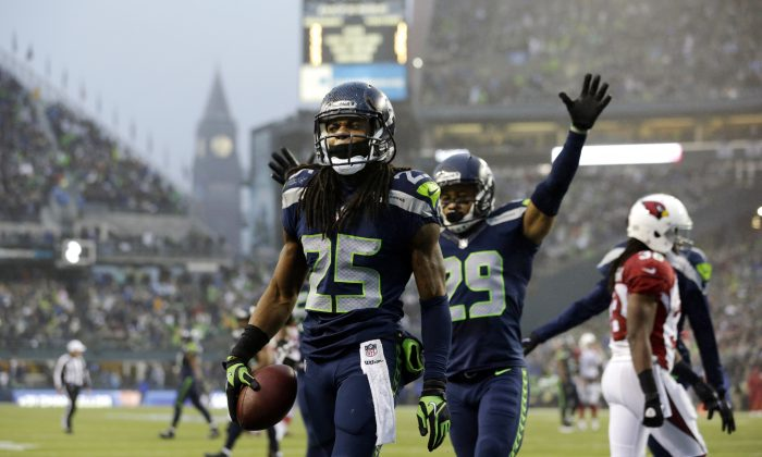 Seattle Seahawks Richard Sherman (25) comes up with the football as Seahawks' Earl Thomas (29) celebrates after Sherman intercepted an Arizona Cardinals pass in the second half of an NFL football game, Sunday, Dec. 22, 2013, in Seattle. (AP Photo/Elaine Thompson)