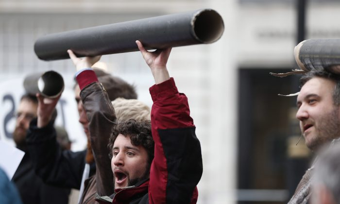 Protesters hold mock-ups of pipes during a demonstration near the G8 foreign ministers' meeting in central London, Thursday, April 11, 2013. (AP Photo/Lefteris Pitarakis)