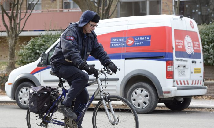 A postal worker rides past a Canada Post van in Toronto on Wednesday, Dec. 11, 2013. Opposition parties are criticizing the Crown corporation's plans to phase out home delivery within the next five years, replacing foot delivery with community mail boxes. (The Canadian Press/Frank Gunn)