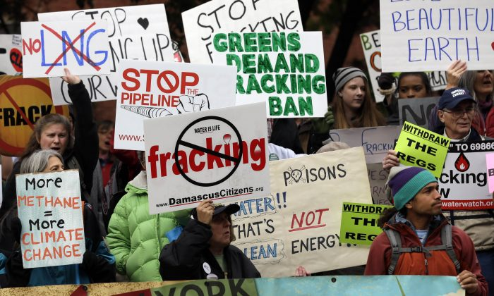 In this Oct. 30, 2013, photo, people hold signs during a rally against hydraulic fracturing for natural gas, or fracking, in Albany, N.Y. (AP Photo/Mike Groll)