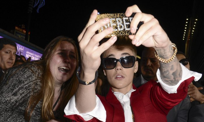 "In this Dec. 18, 2013 file photo, singer Justin Bieber takes a ""selfie"" with a fan at the premiere of the feature film ""Justin Bieber's Believe"" at Regal Cinemas L.A. Live  in Los Angeles. (AP Photo/Dan Steinberg, Invision)"