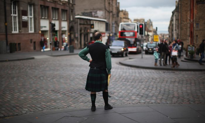 A man dressed in a kilt waits to cross the Royal Mile on February 21, 2012 in Edinburgh, Scotland. A favourite with visitors and one of the busiest streets in the city, the Royal Mile runs from Edinburgh Castle at the top down to Holyrood Palace at the foot. (Jeff J Mitchell/Getty Images)