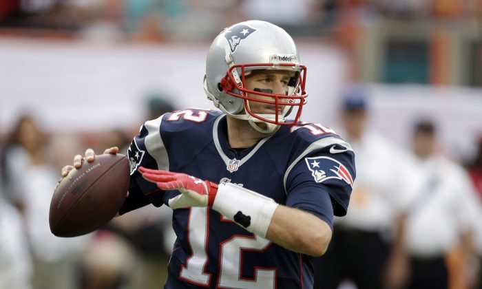 New England Patriots quarterback Tom Brady (12) looks to pass during the second half of an NFL football game against the Miami Dolphins, Sunday, Dec. 15, 2013, in Miami Gardens, Fla. (AP Photo/Lynne Sladky)