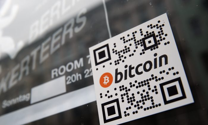 A sticker on the window of a local pub indicates the acceptance of bitcoins for payment on April 11, in Berlin, Germany. More than 1,000 brick and mortar businesses accept it, so do more than 10,000 online merchants. Why? Because its transaction costs are much lower than other forms of payment, such as credit cards. (Sean Gallup/Getty Images)