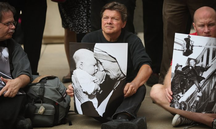 Fired Chicago Sun-Times photographer Al Podgorski holds a picture of Mother Teresa he took, during a photo exhibit of images taken by the newspaper's former photography staff outside the Chicago Sun-Times Media's offices, Chicago, July 30. (Scott Olson/Getty Images)