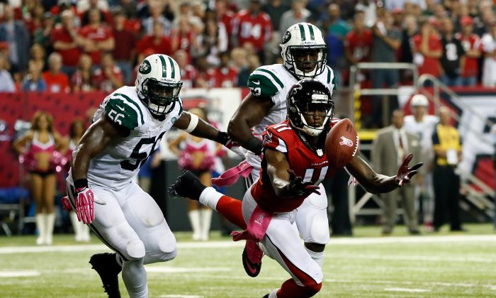 Wide receiver Julio Jones #11 of the Atlanta Falcons tries to make a catch as inside linebacker DeMario Davis #56 and inside linebacker David Harris #52 of the New York Jets defend during their game at the Georgia Dome on October 7, 2013 in Atlanta, Georgia. (Photo by Kevin C. Cox/Getty Images)