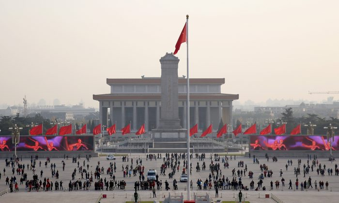 "Tourists visit Tiananmen Square on Nov. 14, 2013, in Beijing, China. On Jan. 23, 2001, the Chinese regime staged ""self-immolations"" by alleged Falun Gong practitioners and then featured video of the fabricated event in propaganda attacking the group. (Feng Li/Getty Images)"