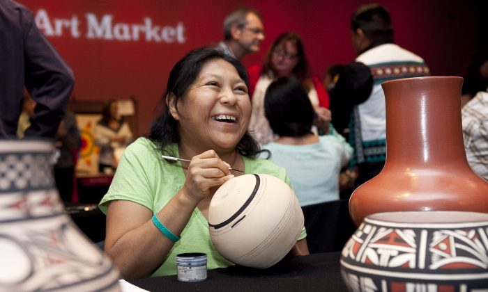 Nona Latona paints pottery at the Native American Art Market, Dec. 6. (Samira Bouaou/Epoch Times)