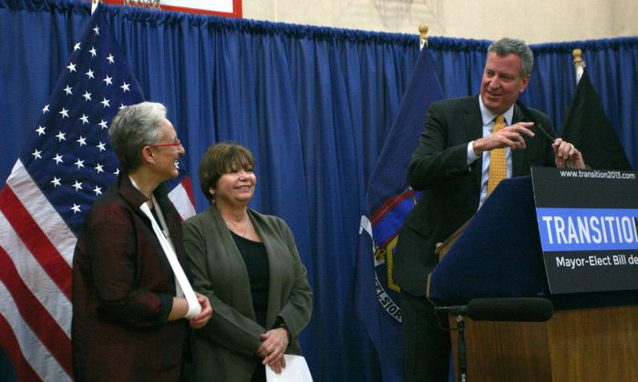 Mayor-elect Bill de Blasio draws a laugh from Lilliam Barrios-Paoli (L), the incoming Deputy Mayor for Health and Human Services, and Gladys Carrion, the incoming Commissioner for the Administration of Children's services at the Henry Street Settlement on the Lower East Side on Dec. 22. (Ivan Pentchoukov/Epoch Times)