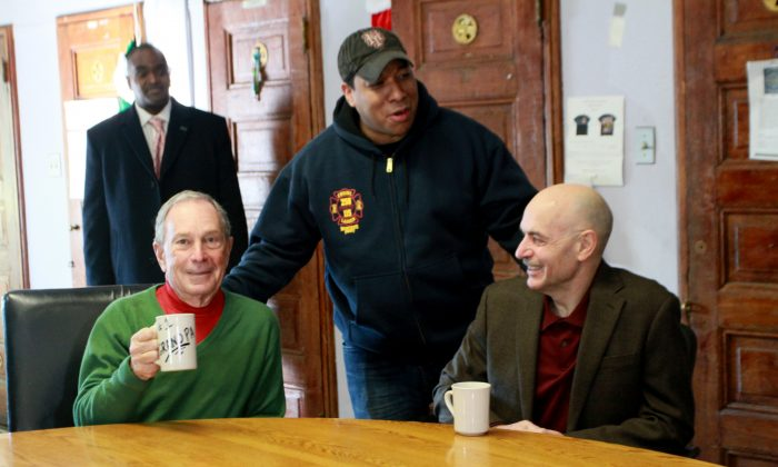 """Mayor Michael Bloomberg (L) holds a gift mug with """"#1 Grandpa"""" written on it at a firehouse in Queens on Dec. 25. (Ivan Pentchoukov/Epoch Times)"""