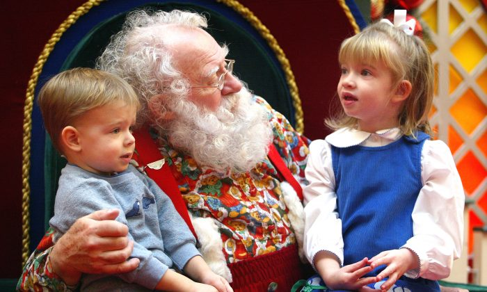NILES, IL - DECEMBER 19: Sporting a natural white beard, Santa Claus visits with Ian, 2, and sister Devin Rachiele, 4, December 19, 2003 at Golf Mill Mall in Niles, Illinois. Santa says that the children that visit him feel more comfortable when he is not wearing his traditional Santa coat and hat. (Photo by Tim Boyle/Getty Images)