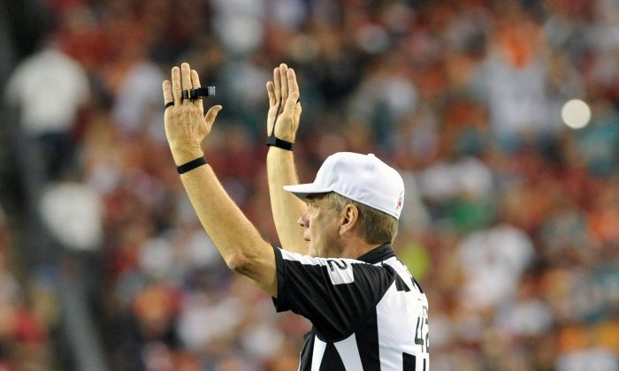 NFL referee Jeff Triplette signals a touchdown as the Miami Dolphins play against the Tampa Bay Buccaneers November 11, 2013 at Raymond James Stadium in Tampa, Florida. Tampa won 22 - 19.  (Photo by Al Messerschmidt/Getty Images)