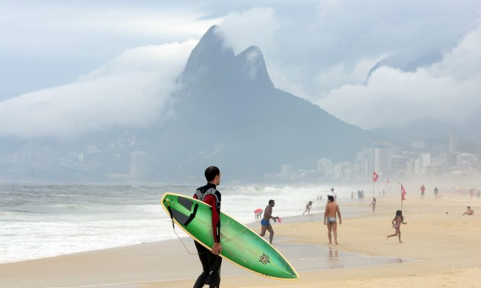 A surfer walks in Ipanema beach on a cloudy day in Rio de Janeiro, on November 30, 2013 Brazil. (CHRISTOPHE SIMON/AFP/Getty Images)