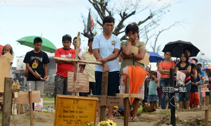 Relatives of victims of Tyhpoon Haiyan gather at a mass grave in Palo, Leyte, on Dec. 8, 2013 to commemorate one month since the typhoon.  (Noel Celis/AFP/Getty Images)
