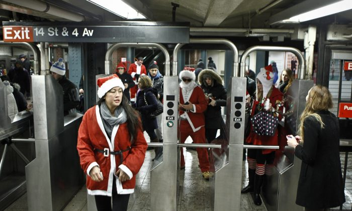Revelers dressed as Santa Claus enter the 14th street subway station during the annual SantaCon bar crawl event on December 14, 2013 in New York City. The SantaCon annual event occurs worldwide in more than 300 cities in 44 countries. In New York some community groups have established a 'Santa Free' zone that urges bars not to serve alcoholic beverages to people participating in order to dissuade incidents of public vomiting and urination in the streets. (Photo by Kena Betancur/Getty Images)