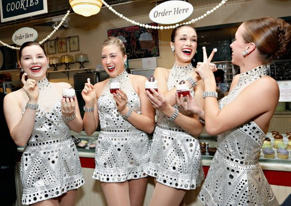 "Radio City Rockettes Danielle Betscher, Elizabeth Bork, Jessica Davison, and Megan Miller attend the Magnolia Bakery ""Rockette Red Velvet"" cupcake unveiling at Magnolia Bakery Rockefeller Center in New York, Dec. 18, 2013. (Cindy Ord/Getty Images)"