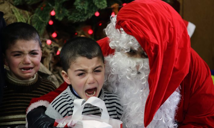 Syrian boys cry as they are pictured with Santa Claus at a kindergarten. (LOUAI BESHARA/AFP/Getty Images)