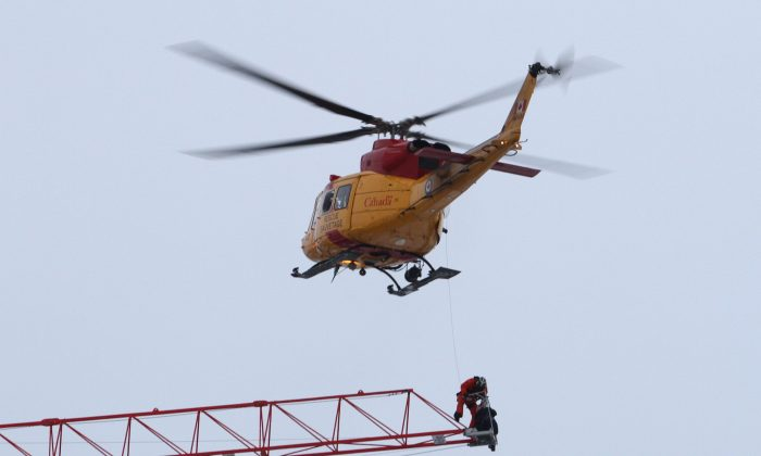A rescue worker is lowered from a Canadian military helicopter as they retrieve Adam Jastrezbski, a crane operator who was stranded atop a crane when fire broke out in an apartment building under construction in downtown Kingston, Ontario, Tuesday, Dec. 17, 2013. (AP Photo/The Canadian Press, Lars Hagberg)