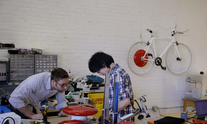 In this Thursday, Dec. 12, 2013 photo, mechanical and software engineer Julian Fong, right, and vehicle design engineer Jon Stevens work on a development to the Copenhagen Wheel, red disk, a human/electric hybrid bicycle engine at Superpedestrian in Cambridge, Mass. (AP Photo/Stephan Savoia)