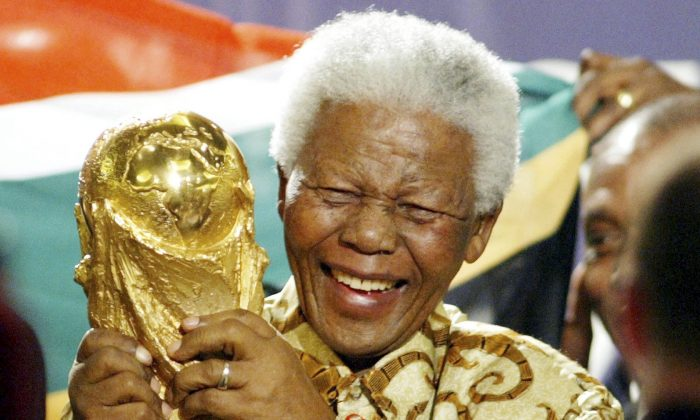 In this May 15, 2004 file photo, former South African President Nelson Mandela lifts the World Cup trophy in Zurich, Switzerland, after FIFA's executive committee announced that South Africa would host the 2010 FIFA World Cup soccer tournament. Mandela was pivotal in helping the country win the right to host the tournament. (AP Photo/Michael Probst, File)