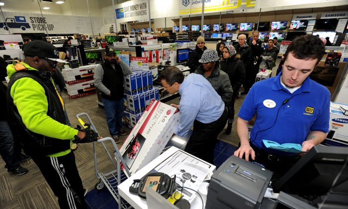 In this Nov. 29, 2013, file photo, Best Buy employee Christopher Gervais, right, rings up a 32-inch LED TV in Dunwoody, Ga.  Sales at U.S. stores dropped 3.1 percent to $42.7 billion for the week that ended on Sunday, Dec. 22, 2013, compared with the same week last year, according to ShopperTrak, which tracks data at 40,000 locations. (AP Photo/David Tulis, File)