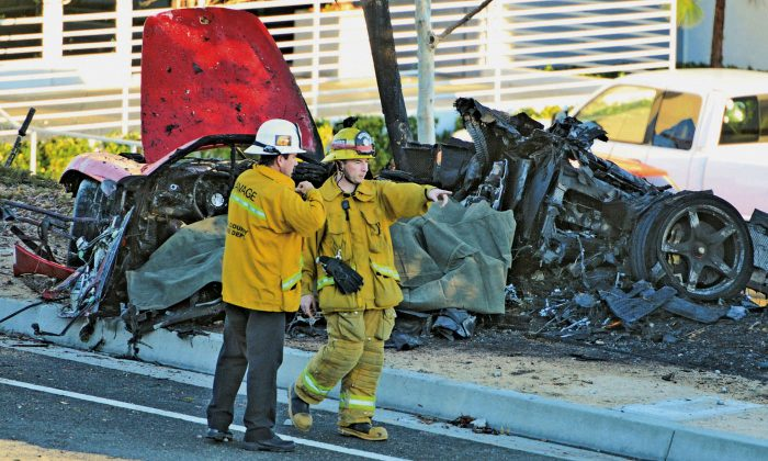 Sheriff's deputies work near the wreckage of a Porsche that Paul Walker and Roger Rodas were in, which crashed into a light pole on Hercules Street near Kelly Johnson Parkway in Valencia, Calif., in this Saturday, Nov. 30, 2013 file photo. (AP Photo/The Santa Clarita Valley Signal, Dan Watson, File)