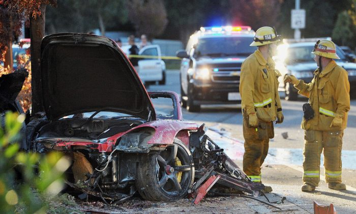 "Sheriff's deputies work near the wreckage of a Porsche that crashed into a light pole on Hercules Street near Kelly Johnson Parkway in Valencia, Calif., on Saturday, Nov. 30, 2013. A publicist for actor Paul Walker says the star of the ""Fast & Furious"" movie series died in the crash north of Los Angeles. He was 40. (AP Photo/The Santa Clarita Valley Signal, Dan Watson)"