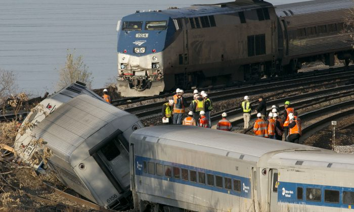 An Amtrak train (top) traveling on an unaffected track, passes a derailed Metro–North commuter train in the Bronx, New York, Dec. 1, 2013. (Mark Lennihan/AP)