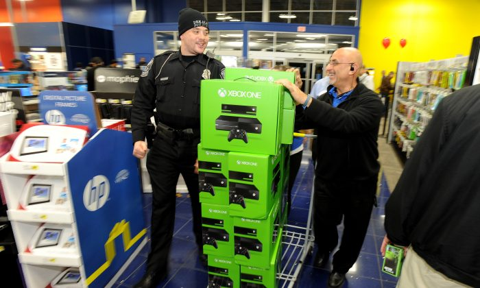 DeKalb police Officer Q.S. Starnes, left, helps Best Buy manager Sammy Abuata wheel in a pallet of Xbox One game sets for a door-buster sale just before midnight on Thanksgiving Day, Thursday, Nov. 28, 2013, in Dunwoody, Ga. (AP Photo/David Tulis)