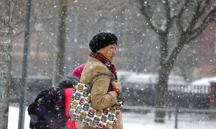 A woman walks her daughter to school as snow falls and temperatures hovered around 8 degrees Wednesday Dec. 4, 2013, in Denver. A wintry storm pushing through the Rockies and Midwest is bringing bitterly cold temperatures and treacherous driving conditions. (AP Photo/Brennan Linsley)
