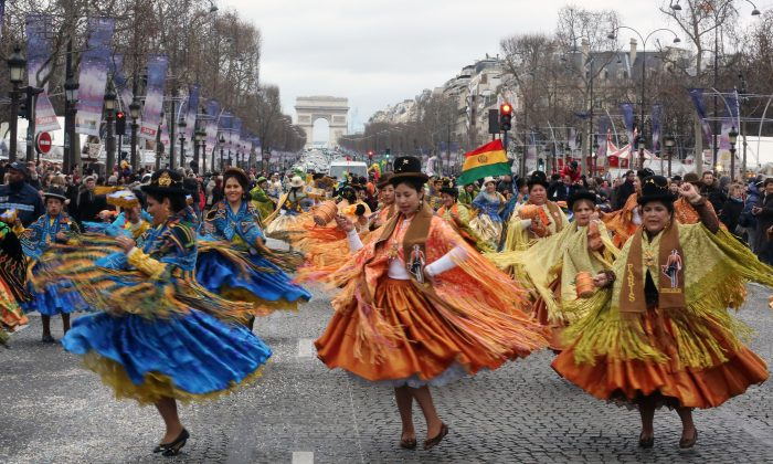 Bolivian dancers perform on the Champs Elysees avenue in Paris, Wednesday Jan. 1, 2014, as part of a parade organized by fairground entertainers to celebrate the New Year. (AP Photo/Remy de la Mauviniere)