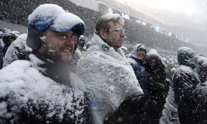 Fans are covered in snow on December 8, 2013 at the Philadelphia Eagles game. Snow is expected to fall in Philly on Tuesday, December 10, the National Weather Service said. (AP Photo/Matt Rourke)