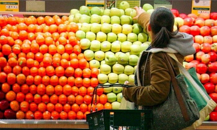 A woman selects apples at a grocery in New York City, file photo. (Stephen Chernin/Getty Images)