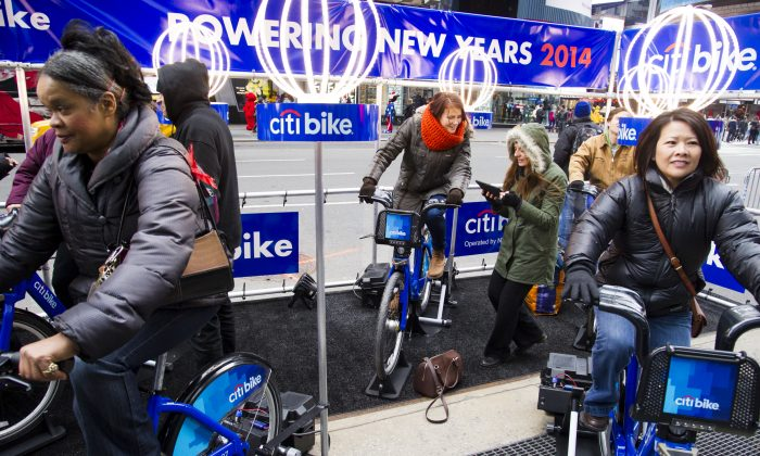 New Yorkers and visitors ride Citi Bikes in Times Square to generate energy to power the New Year's Eve Ball, in New York, Dec. 28, 2013. (Charles Sykes/Invision for Citi/AP)