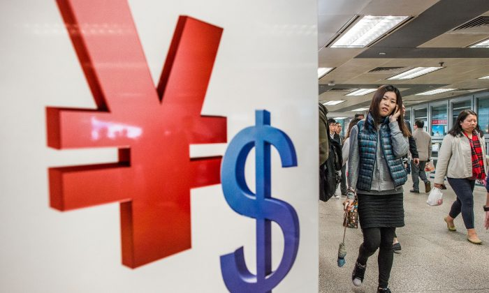A woman walks past Chinese yuan (L) and U.S. dollar symbols in a shopping mall in Hong Kong on Nov. 28, 2012. The yuan has appreciated against the dollar in recent years and has taken a more prominent role in international finance. (Philippe Lopez/AFP/Getty Images)