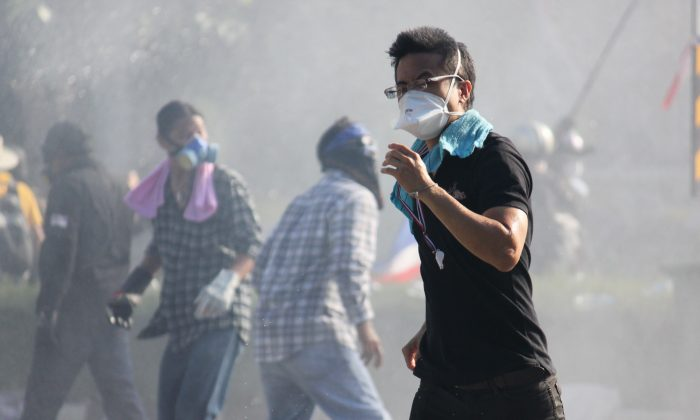 An anti-government protester flees tear gas and a water cannon during a bid to break through a police blockade near Thailand's Government House on Dec. 1, 2013. (Cameron McKinley/Epoch Times)
