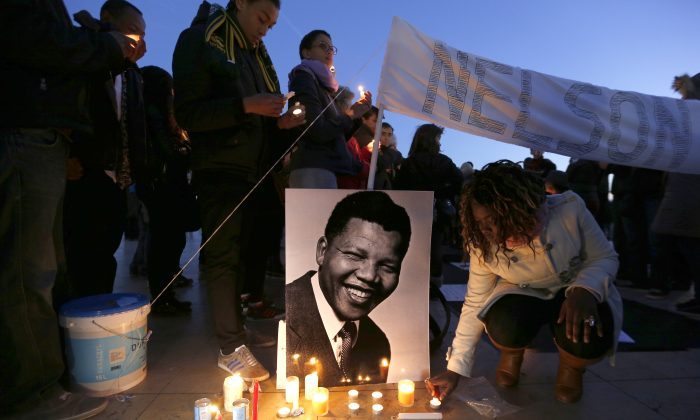A woman lights a candle next to a portrait of late South African President Nelson Mandela during a tribute to Mandela on the Parvis des droits de l'homme (Human Rights square) in central Paris on Dec. 15, 2013. (Francois Guillot/AFP/Getty Images)