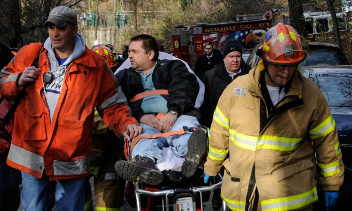 Metro-North Railroad engineer William Rockefeller is wheeled on a stretcher away from the area where the train he was operating derailed in the Bronx, New York, Dec. 1, 2013. (Robert Stolarik/AP)