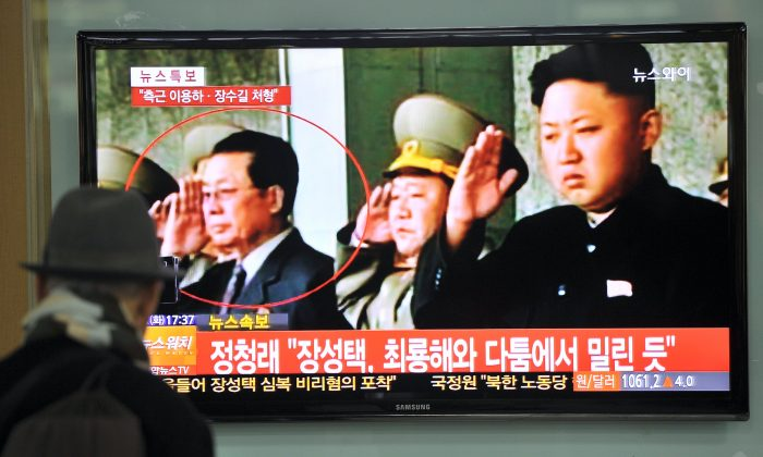 North Korean leader Kim Jong Un (R) and his uncle Jang Song-Thaek (L) on TV in Seoul, South Korea, Dec. 3, 2013. (Jung Yeon-Je/AFP/Getty Images)