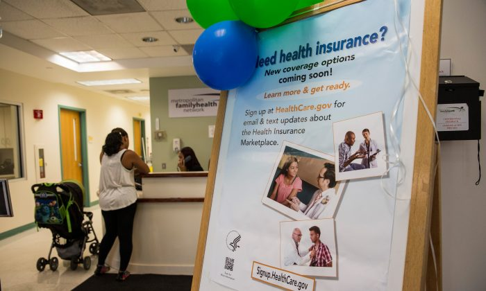 A sign encouraging uninsured people to sign up for the Affordable Care Act, better known as ObamaCare, is displayed for patients as they enter a branch of the Metopolitan Family Health network, in Jersey City, N.J., on Oct. 3, 2013. (Andrew Burton/Getty Images)