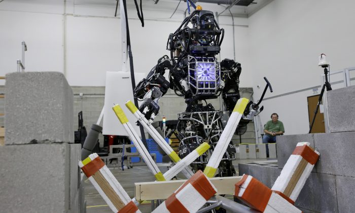 Defense contractor Lockheed Martin's Advanced Technology Laboratories' robot clears a path through debris in Pennsauken, N.J., Thursday, Dec. 12, 2013, during a practice session for a robot competition. The 6-foot tall, 300-pound robot is one of seventeen humanoid robots that will be evaluated Friday and Saturday at Homestead Miami Speedway for how well they can complete tasks including getting into an all-terrain vehicle and driving it, and opening doors. (AP Photo/Mel Evans)