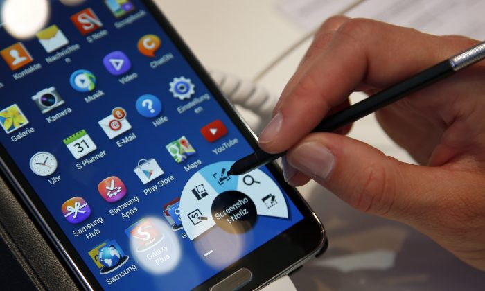 A women works on a Samsung Galaxy Note 3 Smartphone at the IFA, in Berlin, Germany on Friday, Sept. 6, 2013. (AP Photo/Michael Sohn)