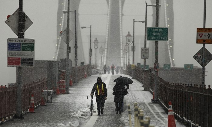 People make their way across the Brooklyn Bridge during the season's first snowstorm on Dec.10, 2013, in New York City. Another storm system is predicted to affect 70 million people from the Midwest to the Northeast this week. (Spencer Platt/Getty Images)