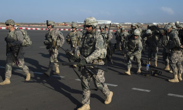 U.S. Army soldiers of the East Africa Response Force (EARF), a Djibouti-based joint team assigned to Combined Joint Task Force-Horn of Africa, prepare to load onto a U.S. Air Force C-130 Hercules at Camp Lemonnier, Djibouti, to support with an ordered departure of personnel from Juba, South Sudan, on Dec. 18, 2013. (Tech. Sgt. Micah Theurich/U.S. Air Force/AP)