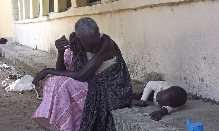 A South Sudanese woman with a child sits on Dec. 25 at the main hospital in Bor which troops loyal to President Salva Kiir re-captured from rebel forces. South Sudan is caught in a political struggle turned ethnic cleansing, with an estimated death-toll in the thousands, and the number of displaced people approaching 100,000. (Samir Bol/AFP/Getty Images)