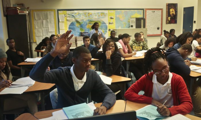 In this file photo students raise hands during a Global Studies class of 10th- and 11th-graders at Bedford Academy High School in New York on Dec. 3, 2013. New York State Education Department (SED) has been under fire for its use of cloud storage to centralize massive amounts of personal data of New York students. (Bebeto Matthews/AP)