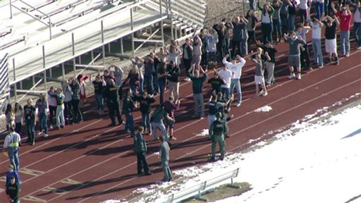 In this still image taken from video provided by Fox 31 Denver, students gather just outside of Arapahoe High School as police respond to reports of a shooting at Arapahoe High School in Centennial, Colo. Friday, Dec. 13, 2013. The suspected gunman killed himself after injuring two students, the county sheriff said. (AP Photo/KDVR)